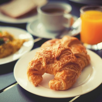 Croissant Breakfast served with black coffee and a breakfast menu such as orange juice jam eggs filling it.